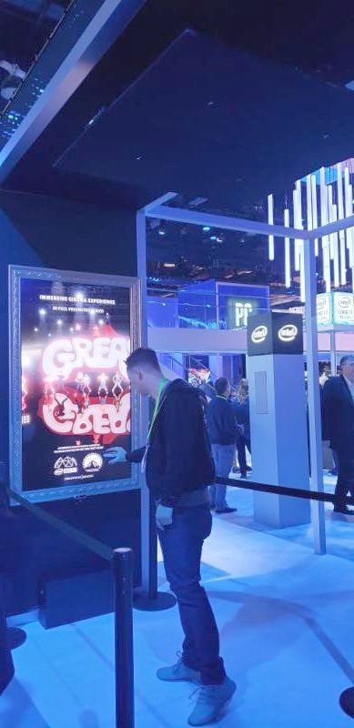 A visitor is immersed in sound under four ceiling-mounted AS-24i speakers at Intel's booth