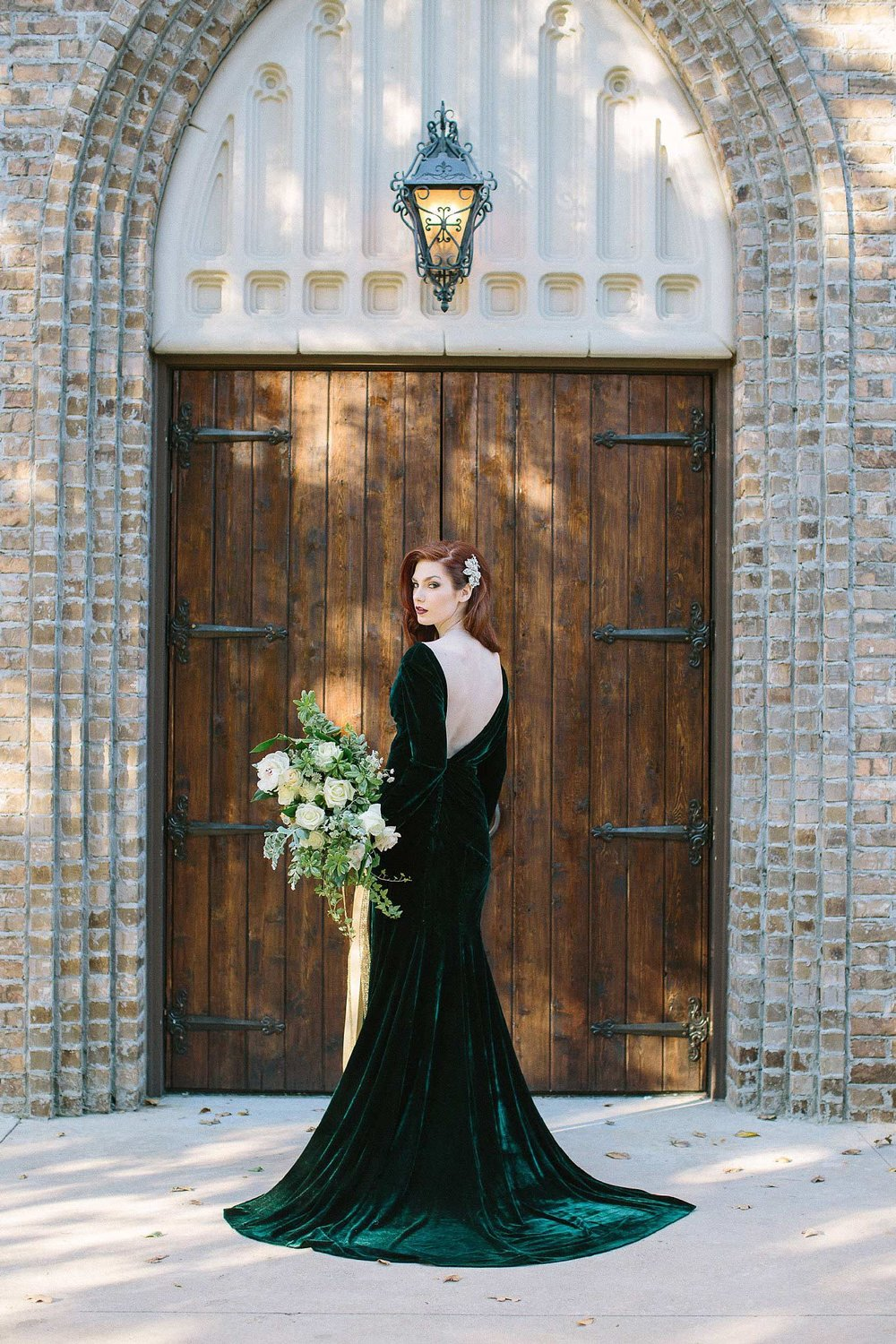aristide mansfield wooden door entry with bridesmaid in green velvet dress