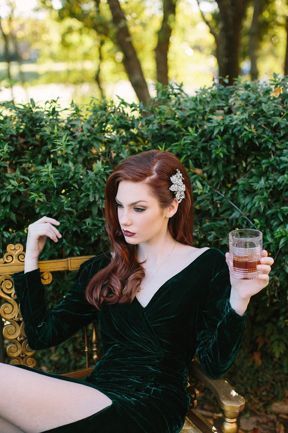 Redhead in velvet green dress drinking whiskey