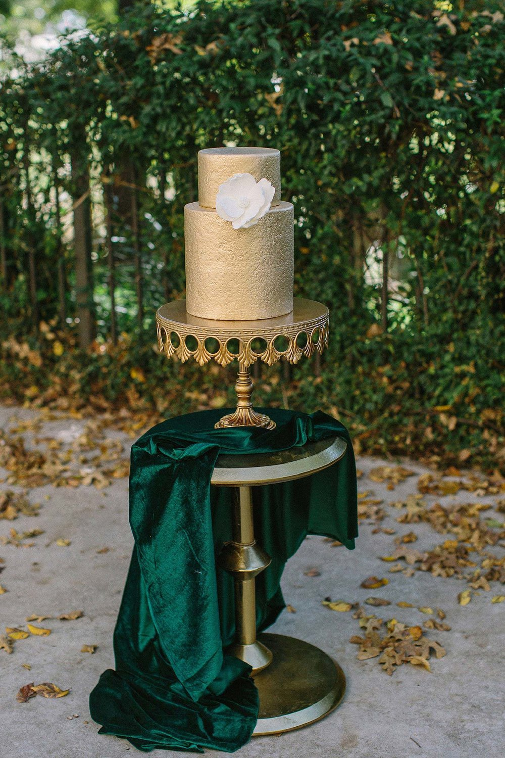aristide mansfield wedding gold wedding cake with white magnolia on green velvet fabric