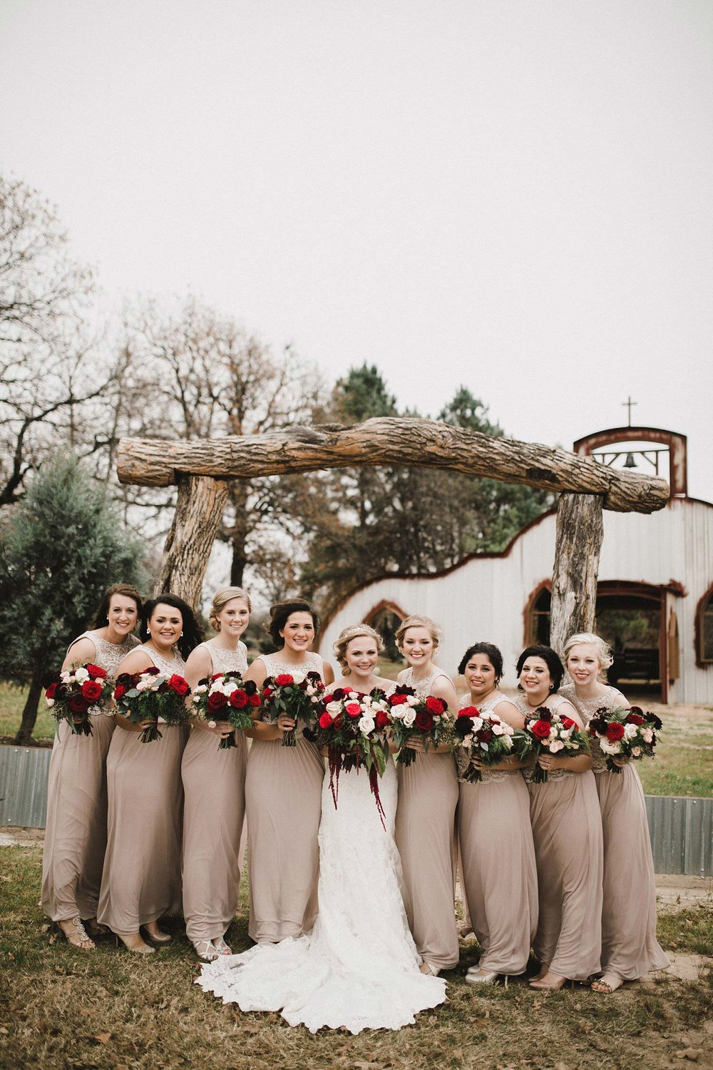 Hollow Hill Farm Event Center Wedding taupe bridesmaid dresses with white and red bouquets