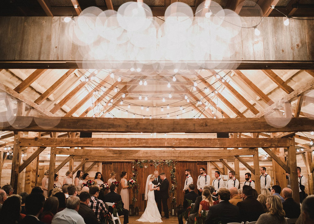 Hollow Hill Farm Event Center Wedding ceremony in wooden barn with cafe lights