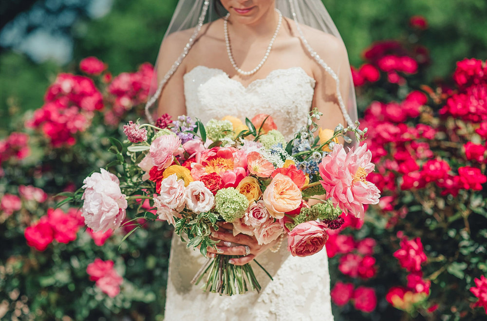The Orchard Azle wedding bride holding colorful bouquet