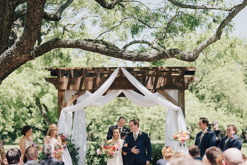The Orchard Azle wedding ceremony at wood trellis with white fabric