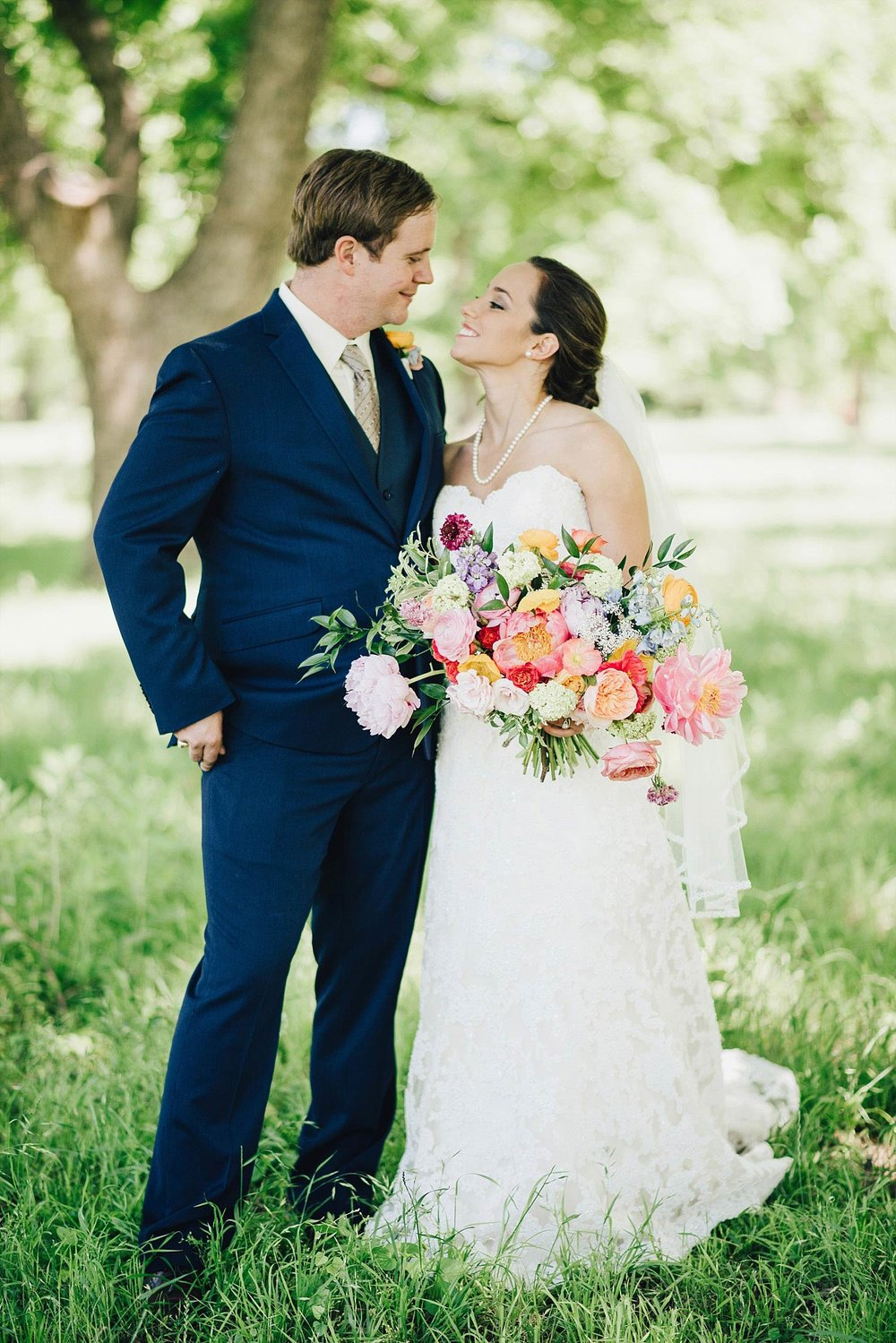 The Orchard Azle wedding bride with colorful bridal bouquet kissing groom