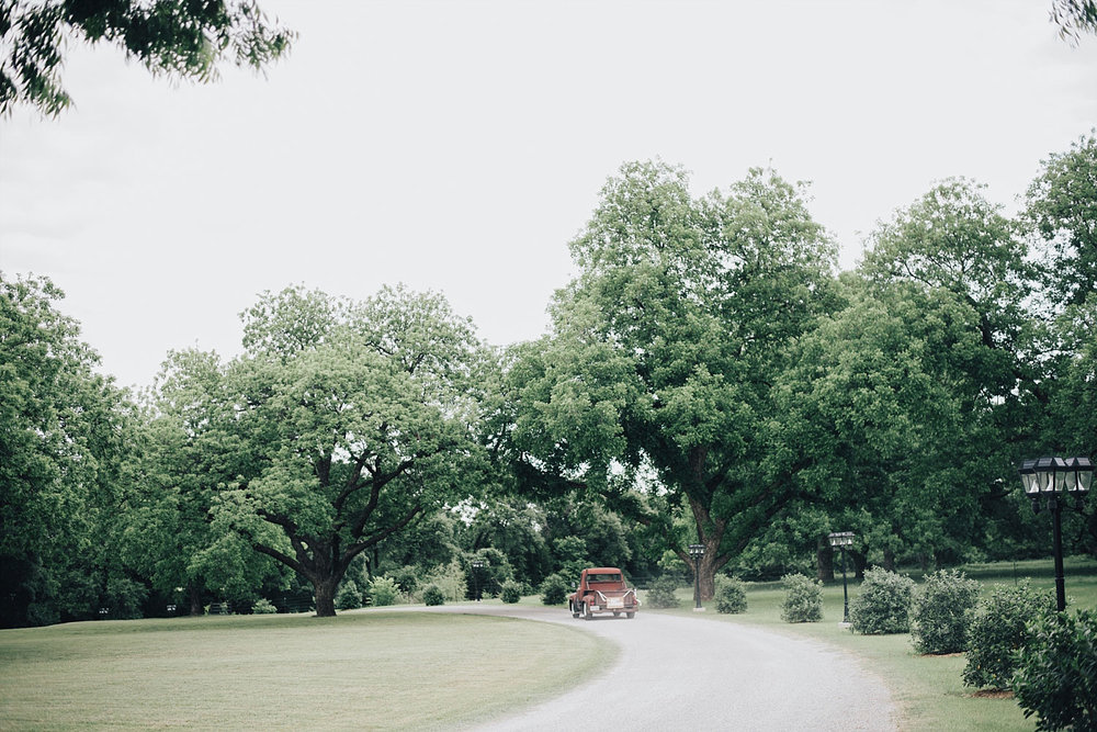 The Orchard Azle wedding vintage truck driving away