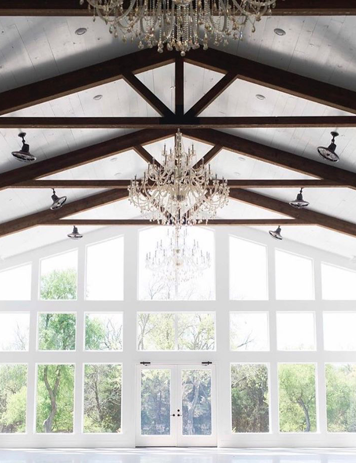 Firefly Gardens event hall white barn with white walls with tall windows and dark wood beams crystal chandeliers