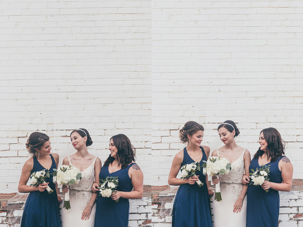 Bride and bridesmaids with navy dresses laughing against a whitewashed brick wall