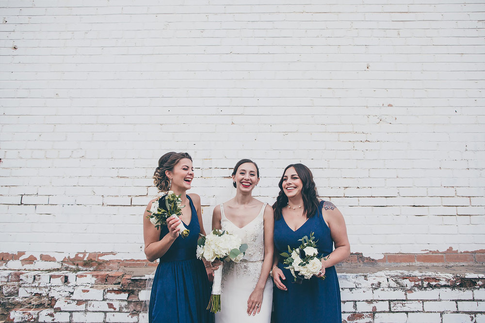 Carlisle Room wedding Bride and bridesmaids laughing against a whitewashed brick wall