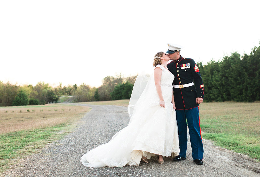 Castle at Rockwall wedding bride and marine groom kissing on gravel road