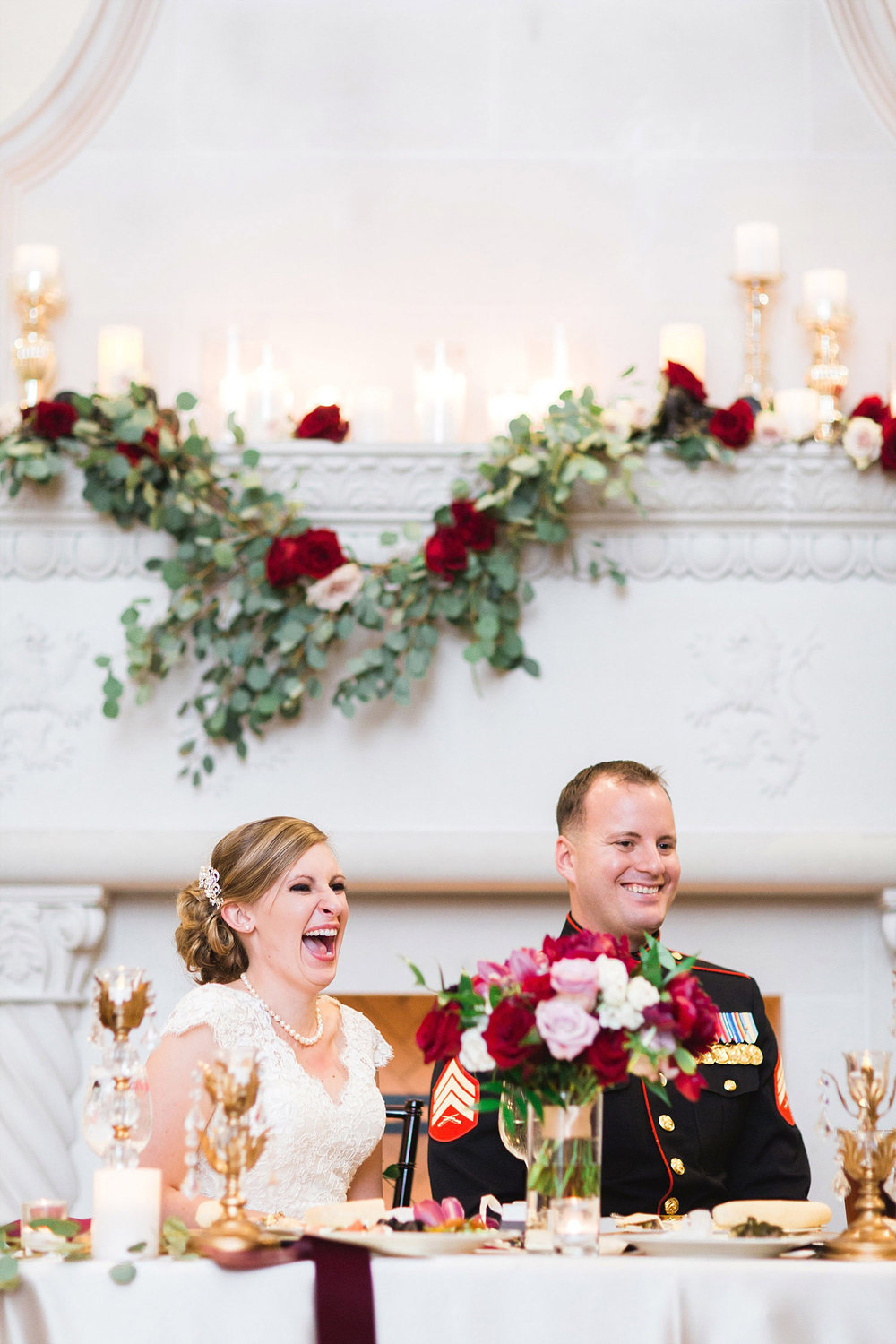 Castle at Rockwall wedding bride and marine groom sitting at sweet heart table in front of fireplace with garland