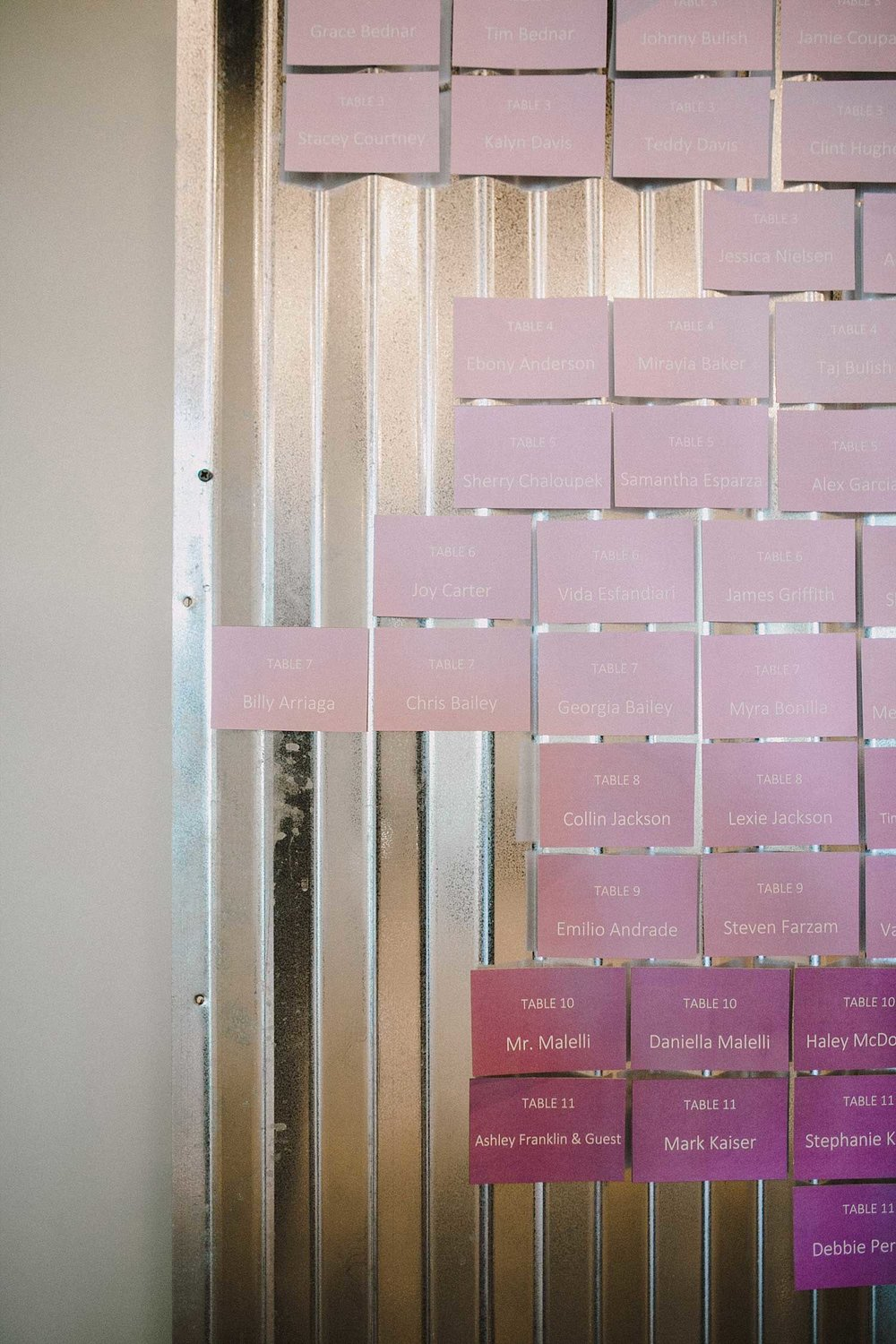 Lavender ombre escort cards on a galvanized metal wall