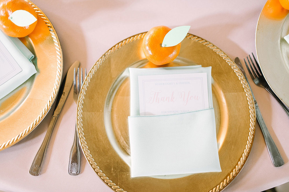 Gold charger place setting with clementine and thank you note at Old Red Museum wedding