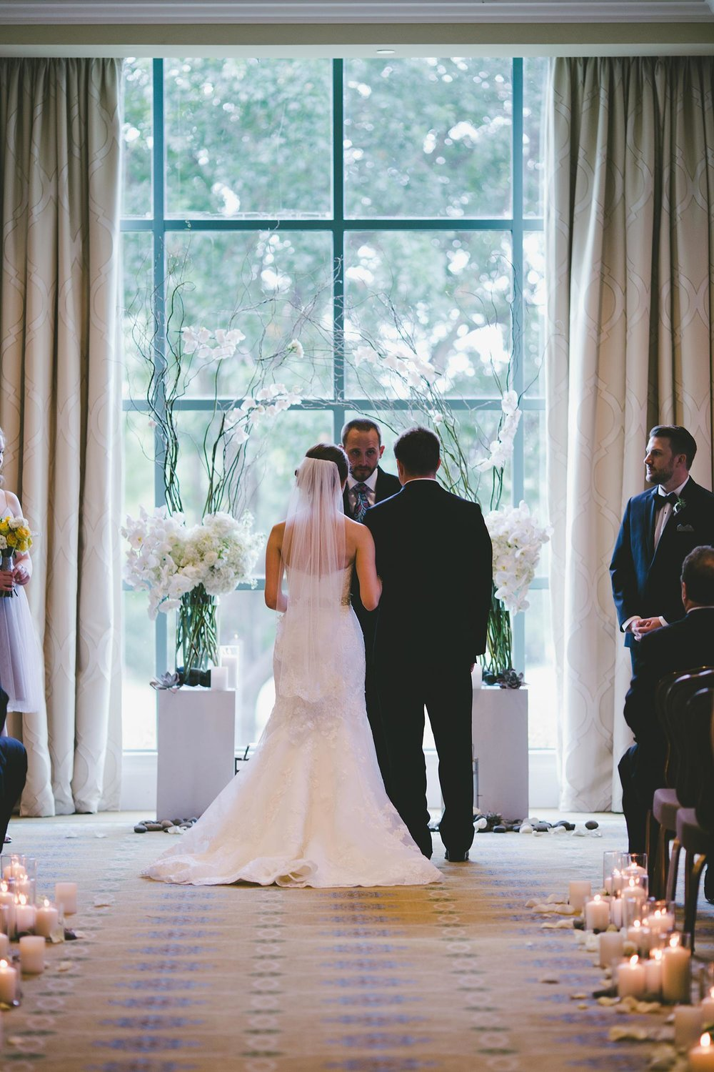 River Crest Country Club ceremony in front of large windows with a white flower and branch archway
