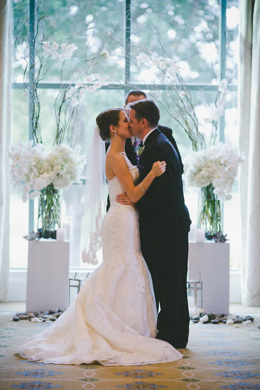 River Crest Country Club ceremony in front of large windows with a white flower and branch archway wih bride and groom kissing