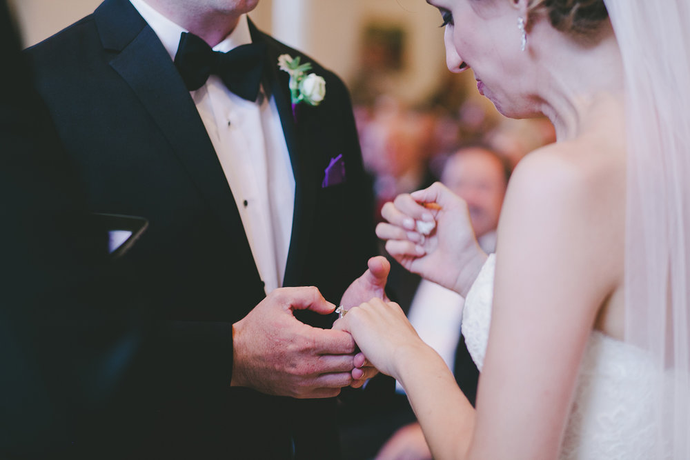 Bride and groom with lavender boutonniere holding hands at ceremony