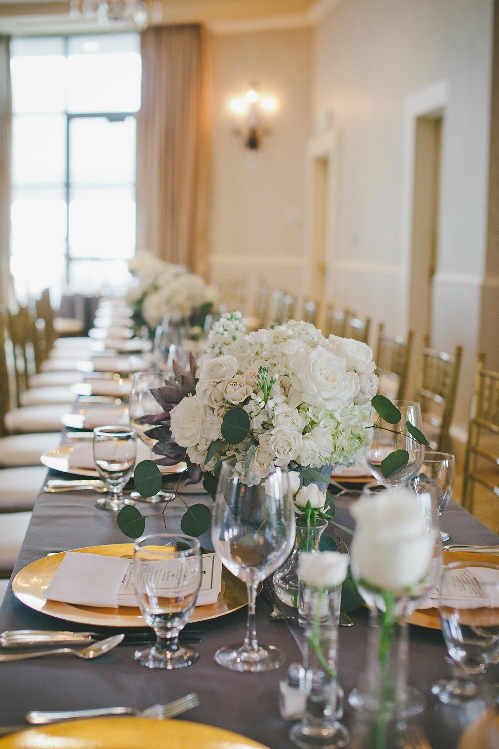 Grey linen table with white flower centerpieces and gold chargers