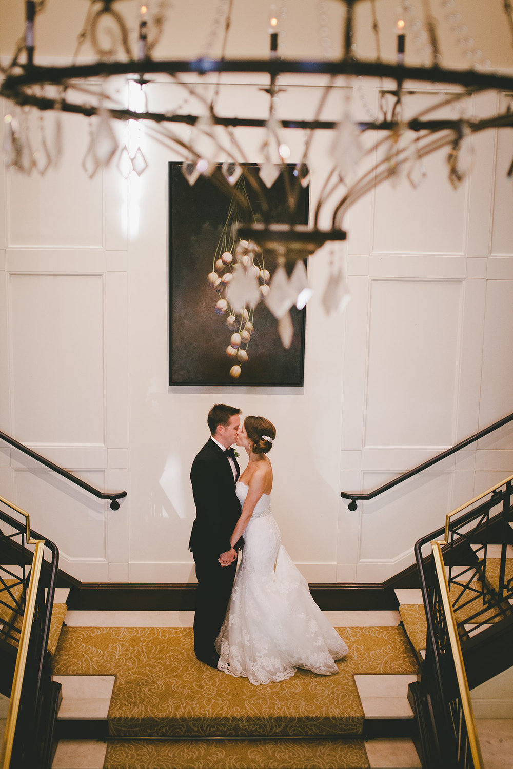 Bride and groom kissing on River Crest Country Club stairway behind crystal chandelier
