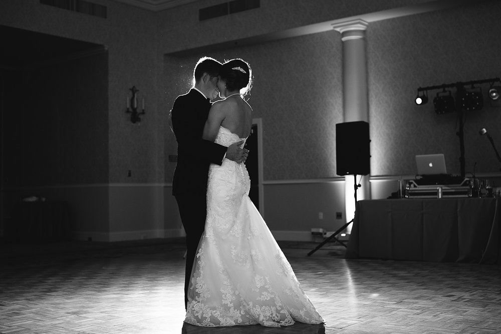 Black and white picture of bride and groom dancing with uplights in the background