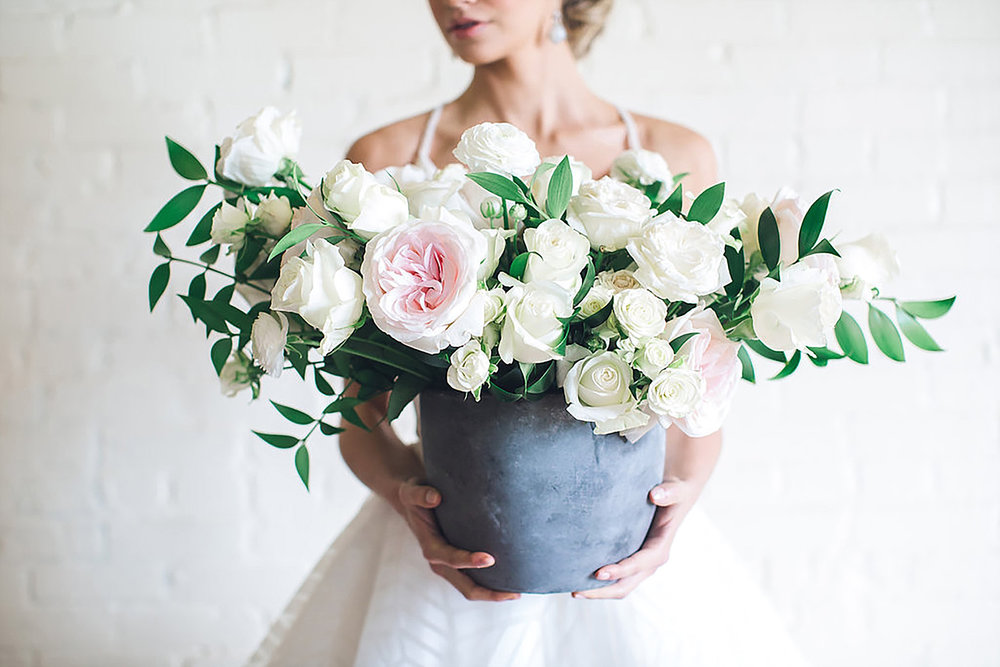 Bride holding white and blush flowers in a concrete vase