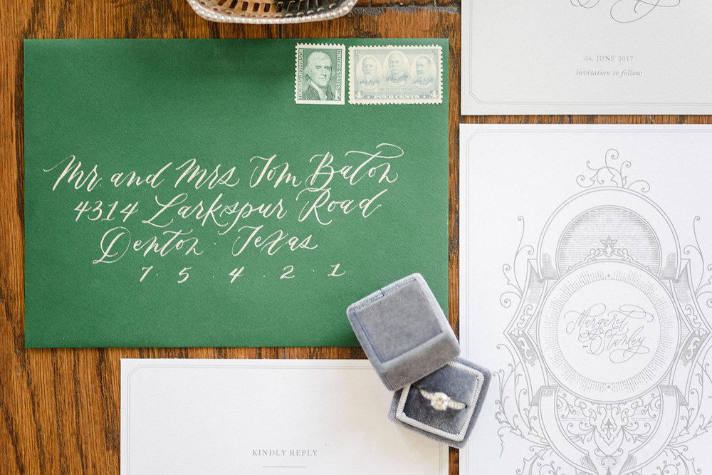 Green envelope wedding invitation with white calligraphy and a light grey velvet ring box