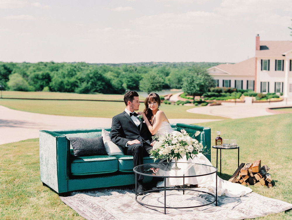 Bride and groom sitting on a emerald sofa at a wedding lounge