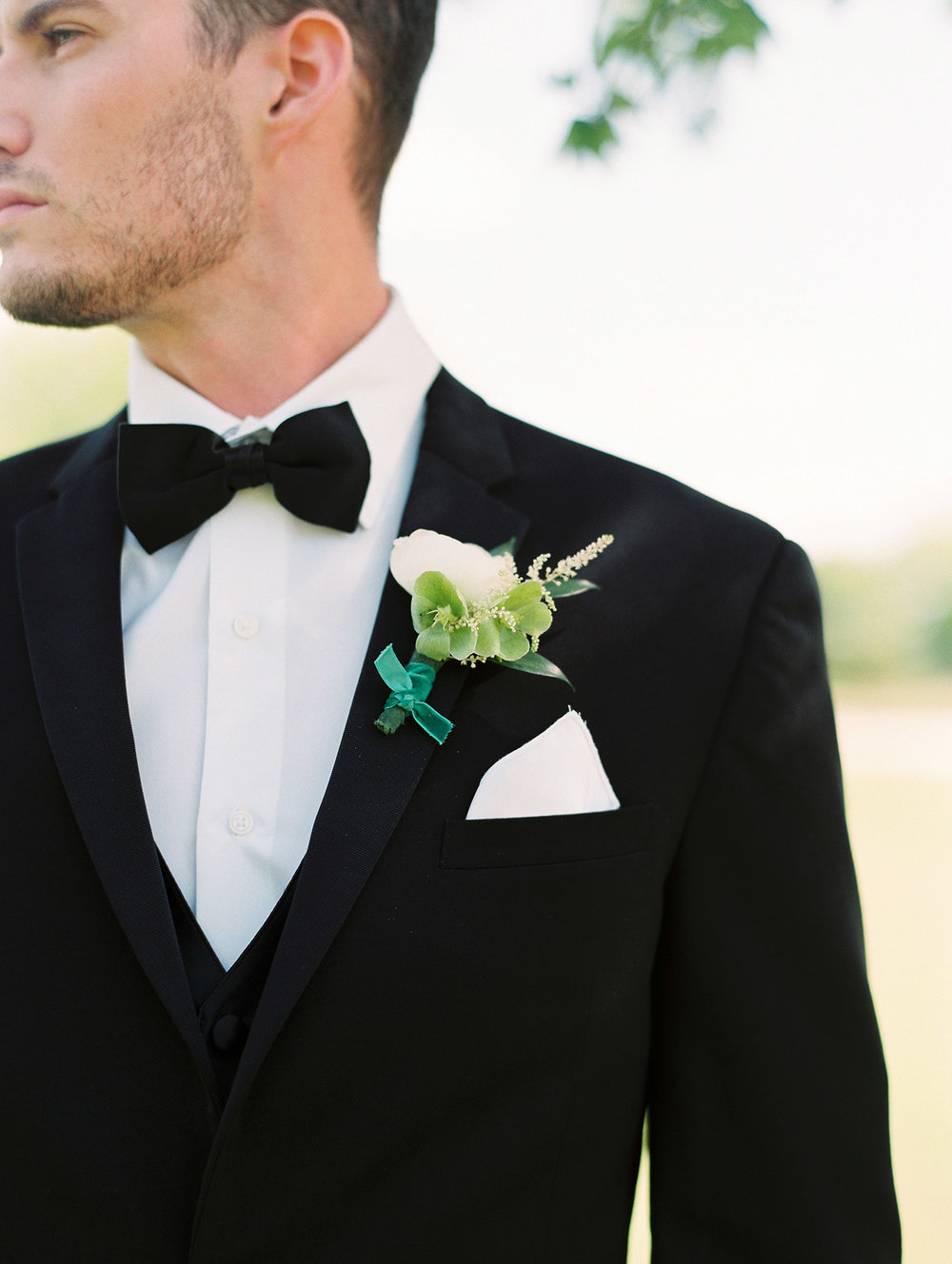Groom in black tuxedo and black bow tie with a white boutonniere and green ribbon