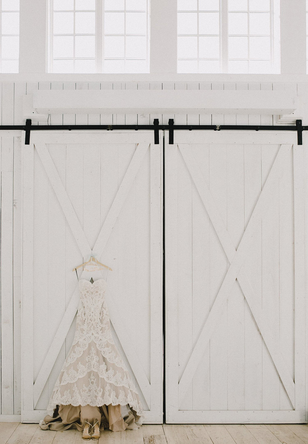 White Sparrow Barn wedding dress hanging on white barn doors with windows above