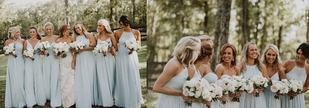 Bridesmaids in long blue bridemaid dresses holding white and blush bridesmaid bouquets at White Sparrow Barn