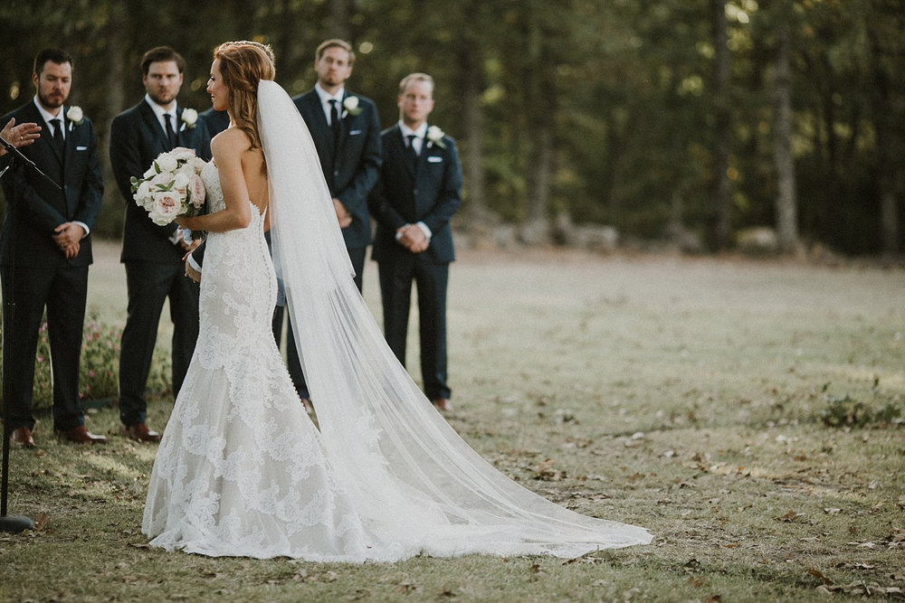 Dallas Cowboy Cheerleader bride at White Sparrow Barn outdoor ceremony with long cathedral veil