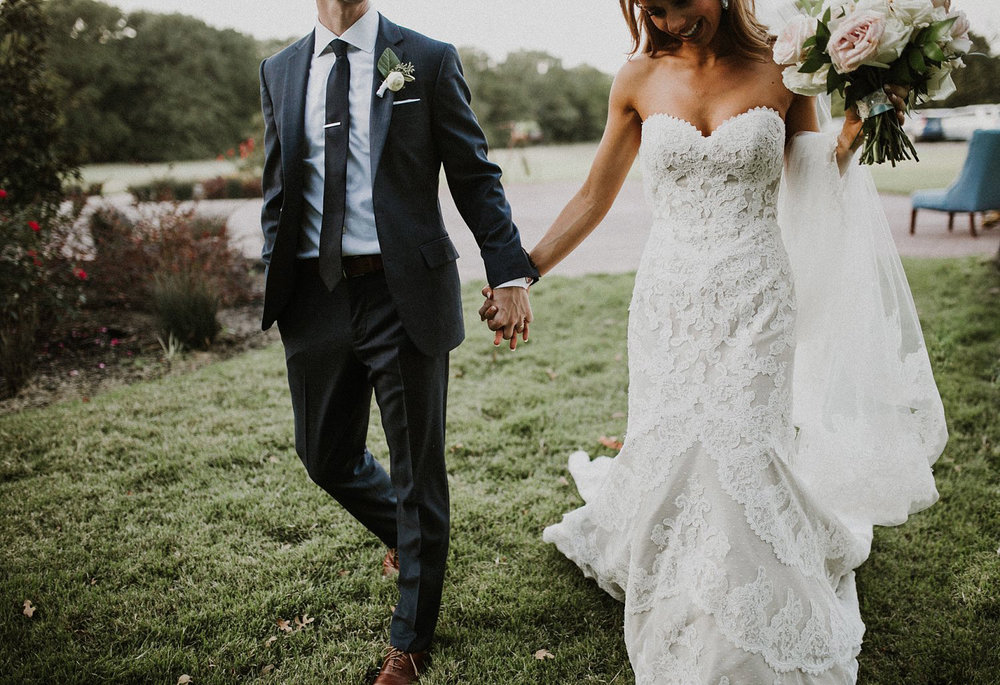 Bride in lace wedding dress holding hand of groom with dark grey suite and tie