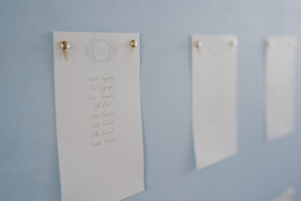 Guest place cards on dusty blue board for White Sparrow Barn wedding