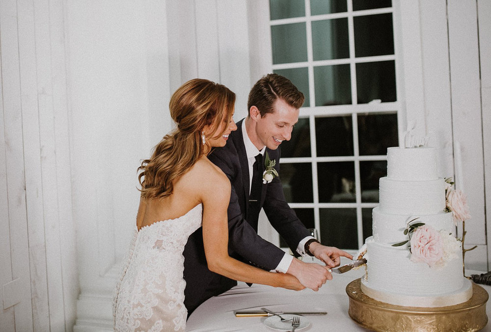 Bride and groom cutting wedding cake in front of white and white shiplap wall
