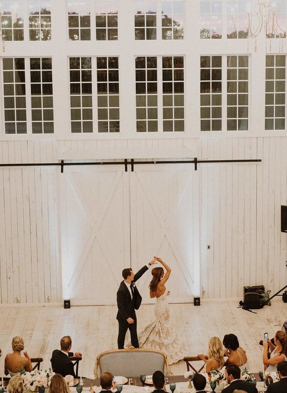 Bride and groom first dance at White Sparrow Barn with white upighting