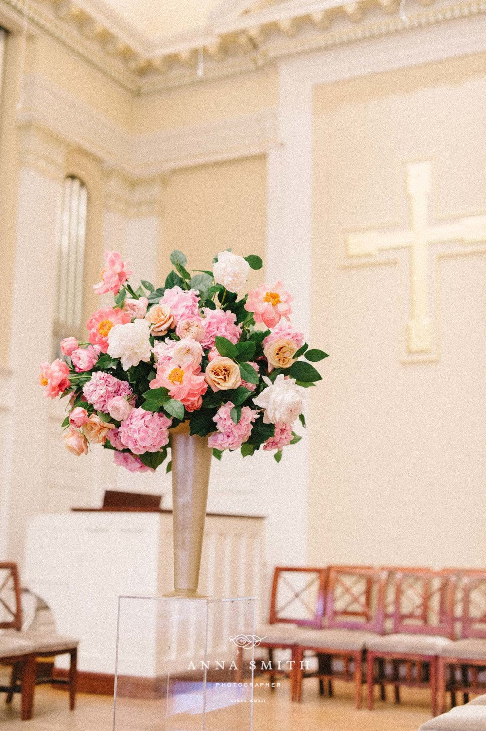 Tall pink garden style arrangement in church ceremony