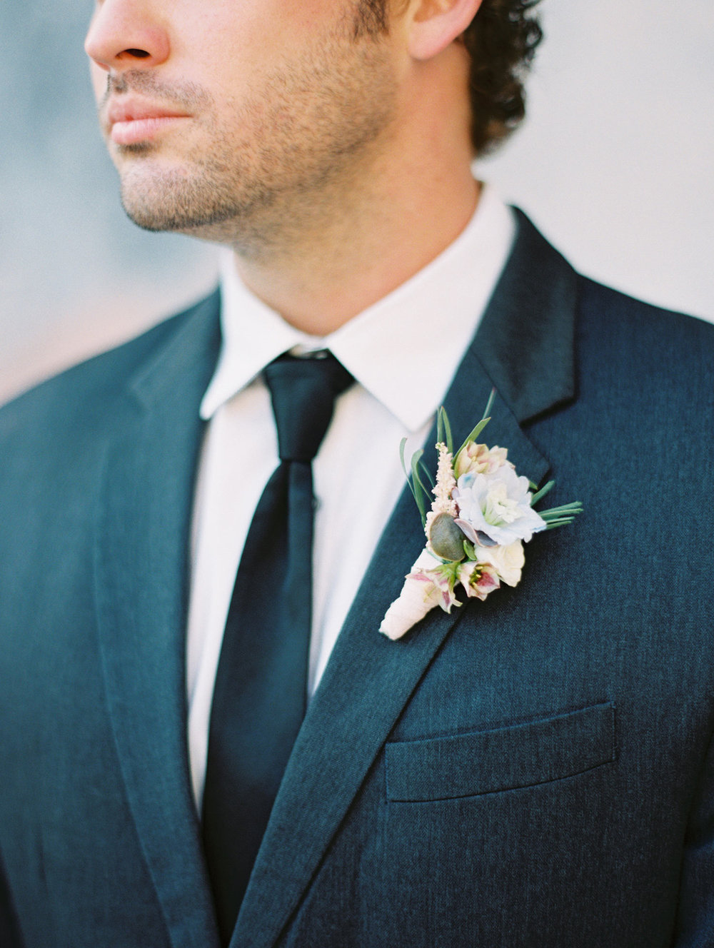 Groom in black tux with a lavender boutinere
