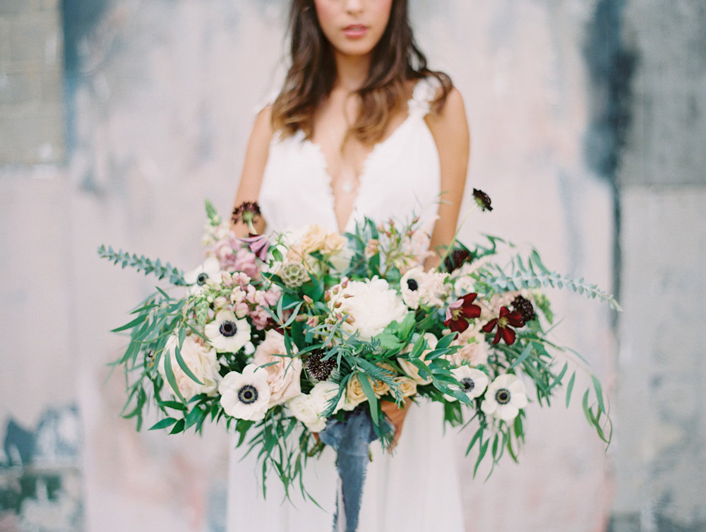 Bride holding a blue white green purple bouquet