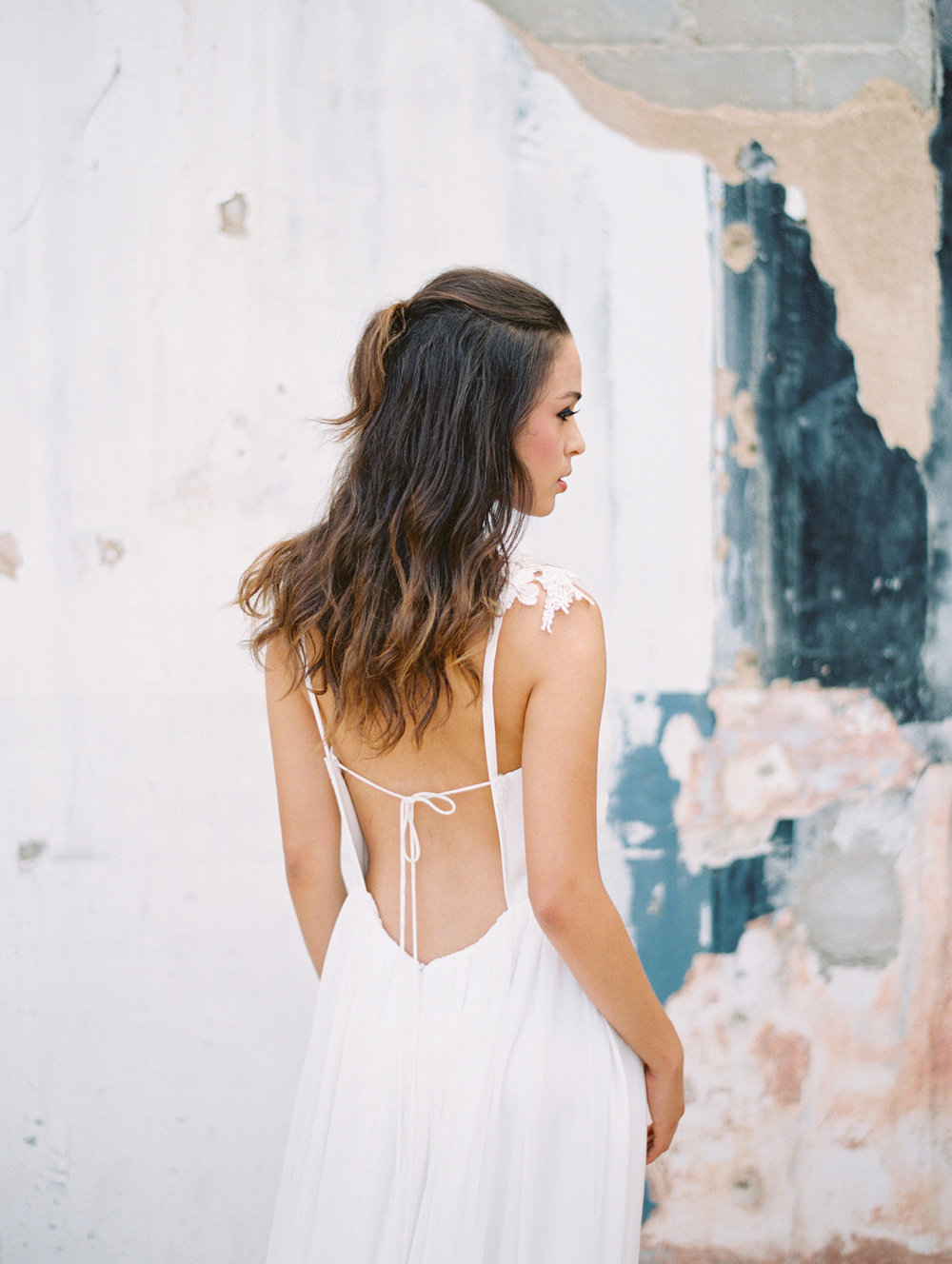 Bride in a low back dress against a textured wall