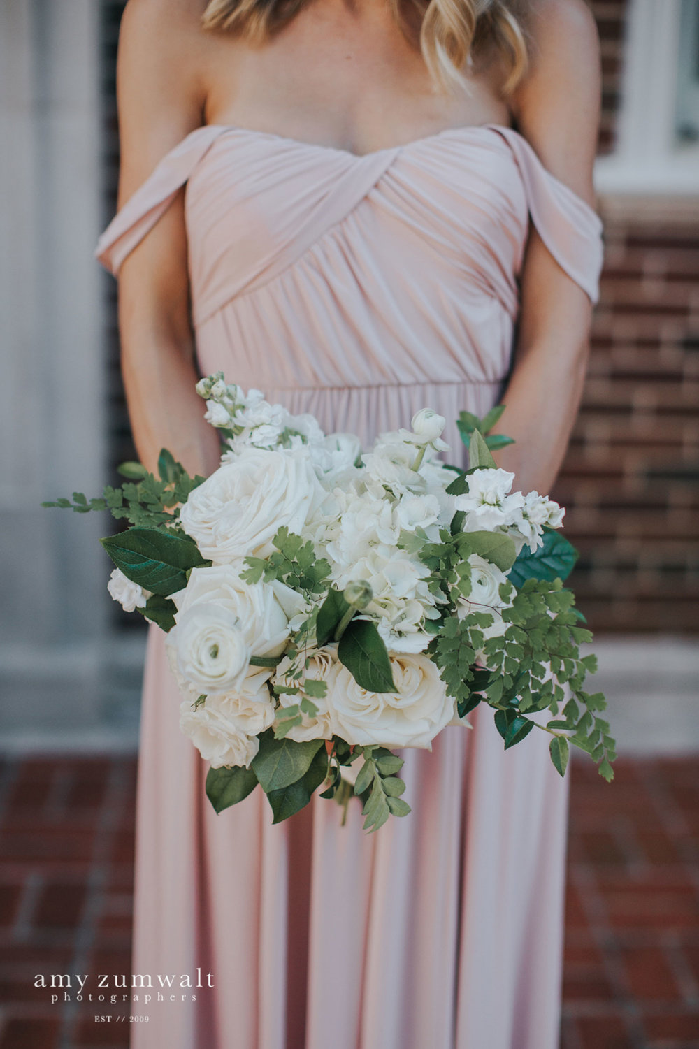 Bridesmaid in mauve bridesmaid dress holding a white and green bouquet