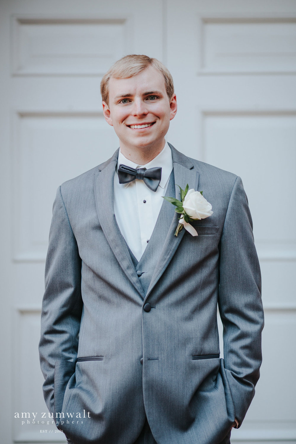 Groom in a grey suite with a blue bowtie
