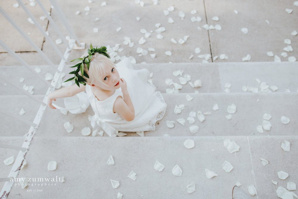 Flower girl sitting in white pedals