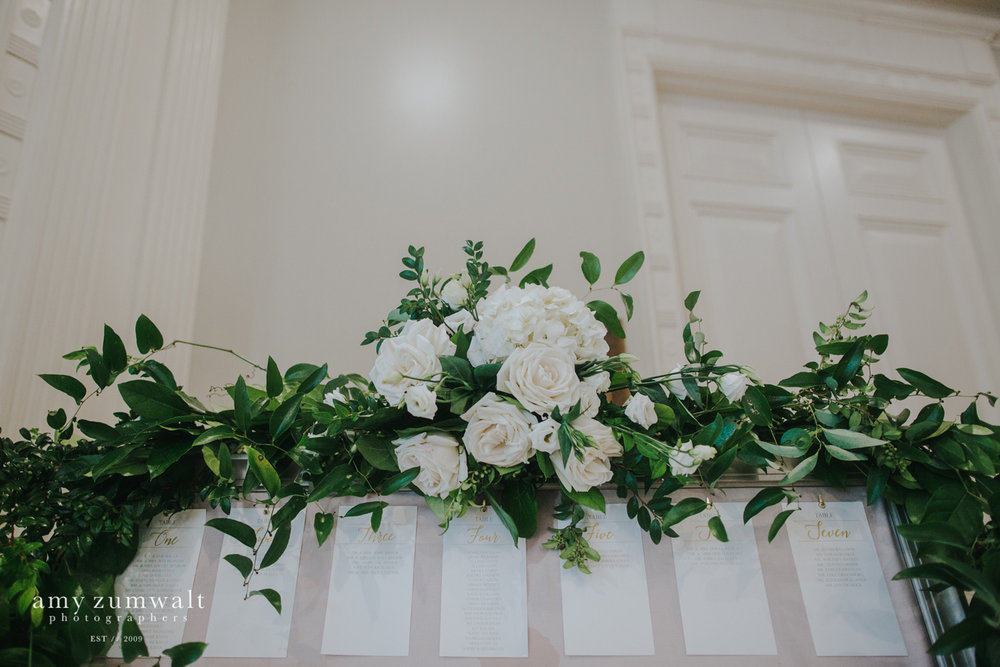 Green garland with white flowers on seating chart