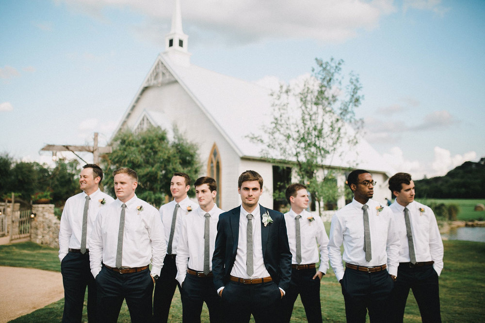 Groom wearing a navy suite with a jacket, and the groomsmen wearing a white shirt and navy pants