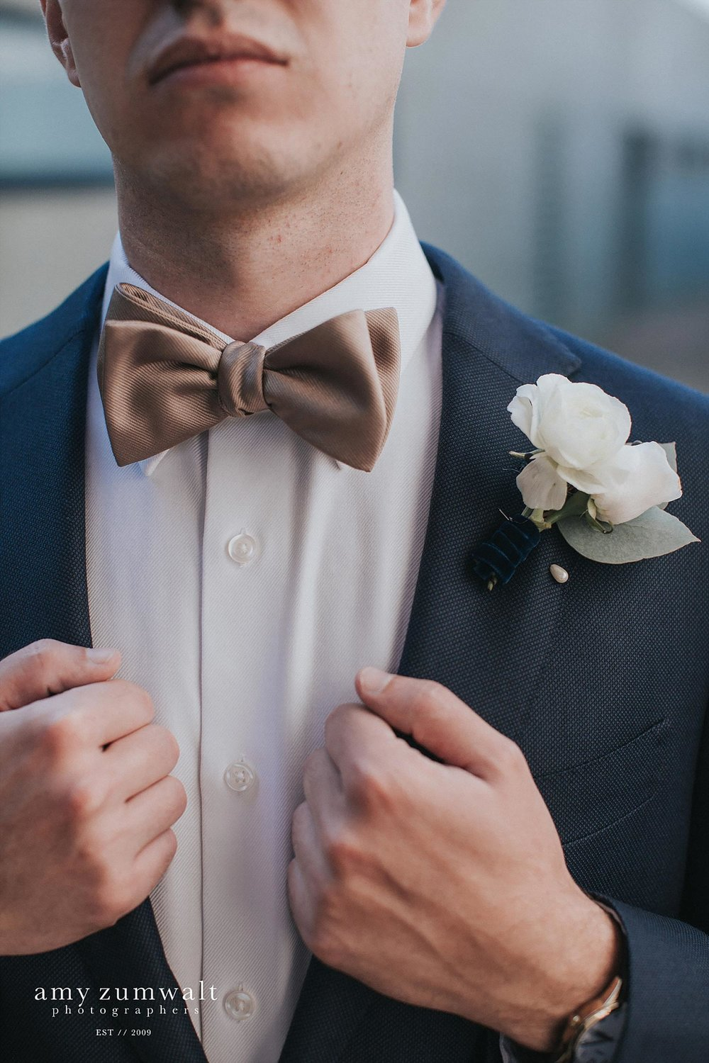groom wearing a navy suit and bowtie with a velvet ribbon boutonniere