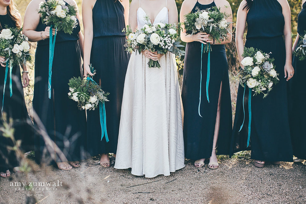 Bridesmaids in low navy dresses with velvet hanging ribbon from their greenery bouquets
