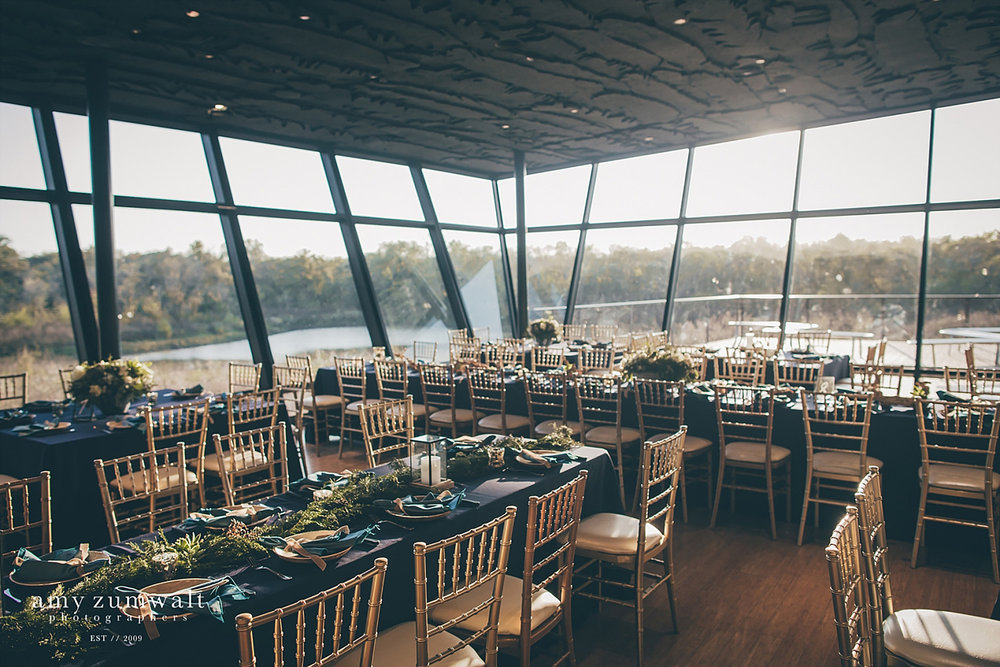 Trinity River Audubon Center wedding reception with gold chairs and navy linens