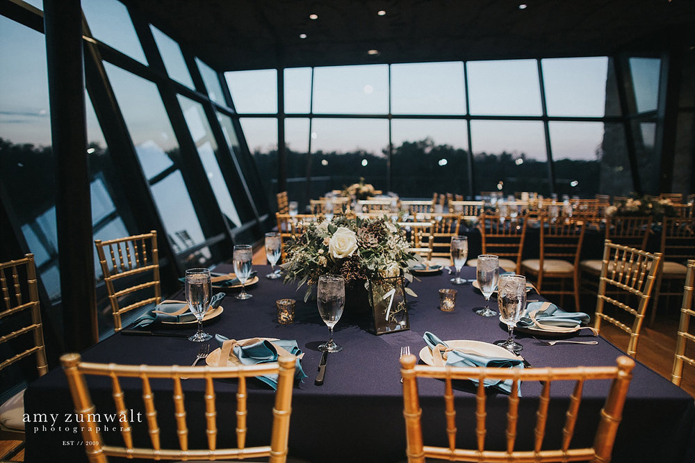 Trinity River Audubon Center wedding with navy linens and greenery arrangments
