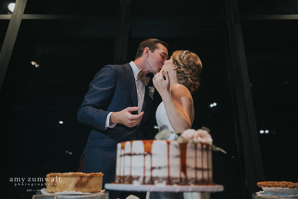 Bride and groom kissing with caramel drip cake at the Trinity River Audubon Center in Dallas TX