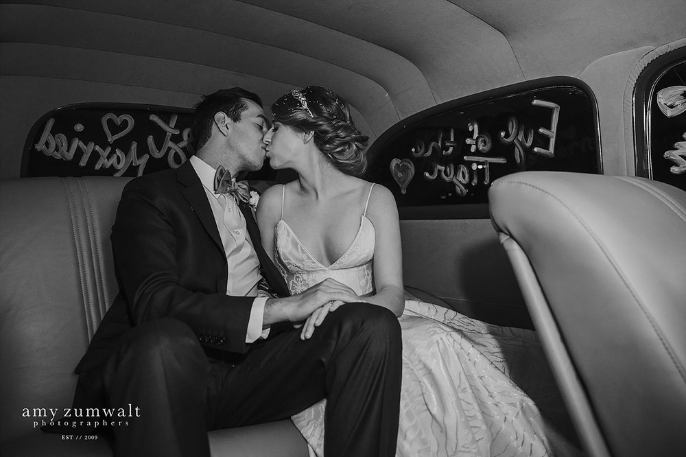 Bride and groom kissing in the exit car at a dallas wedding