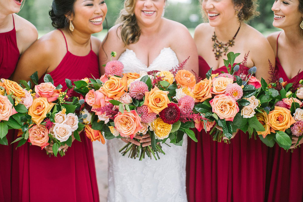 Bridesmaids holding orange coral and apricot bouquets